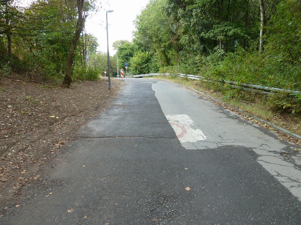 Die Auffahrt zur Lichtscheider Straße im Oktober 2016. Der Fahrbahnbelag ist weit von dem ursprünglichen Zustand entfernt, der Gehweg links wurde nicht mehr rekonstruiert.